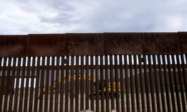 A caterpillar parks between fences at a reinforced section of the U.S.-Mexico border fencing eastern Tijuana, Baja California state, Mexico on Jan. 20, 2021. (Guillermo Arias/AFP via Getty Images)