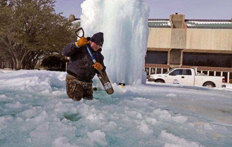 breaks ice on a frozen fountain