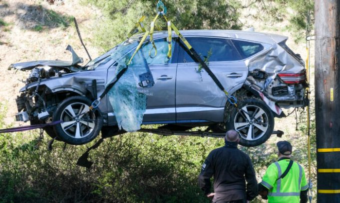 A crane is used to lift a vehicle following a rollover accident involving golfer Tiger Woods in the Rancho Palos Verdes suburb of Los Angeles, Calif., on Feb. 23, 2021. (Ringo H.W. Chiu/AP Photo)