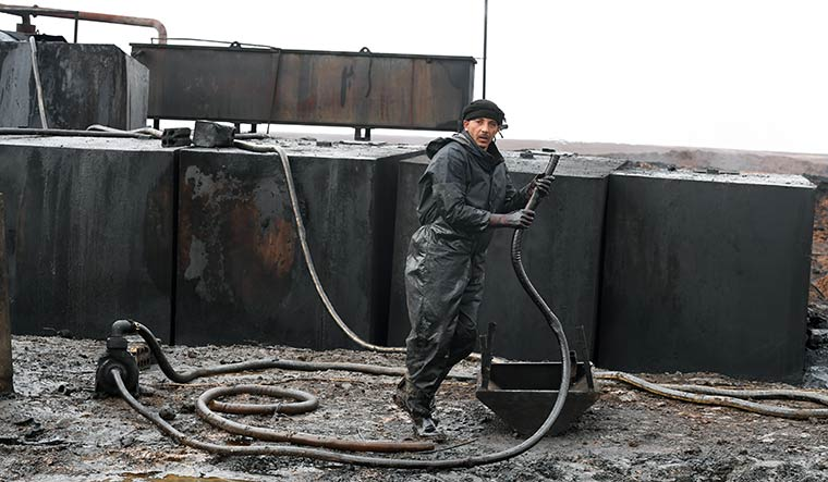 Pay dirt: A worker refining crude oil at Gire Kire village.