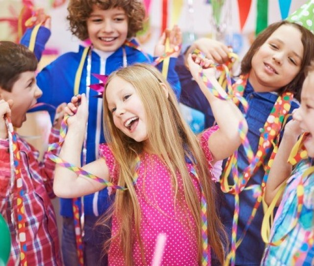 10 Year Old Girl Surrounded By Friends With Streamers Party Blowers And Party Hats