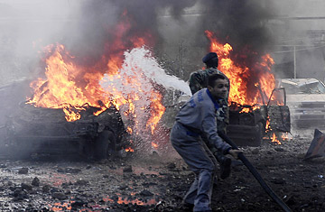 Firefighters extinguish burning cars at the site of an explosion in Beirut, Lebanon Friday, Jan. 25, 2008.