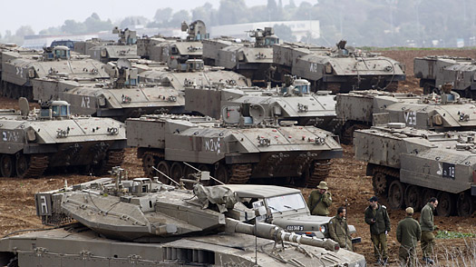 Israeli soldiers stand near armored military vehicles at a staging area just outside the northern Gaza Strip on Dec. 29
