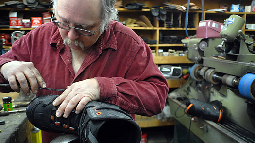 Joe Lynch, owner of Glenn's Shoe Repair, replaces a band of rubber on a snowcat boot at his shop in Kalispell, Mont.
