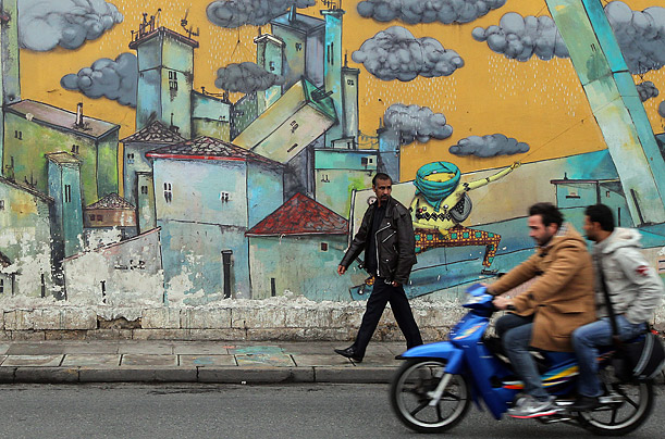 People pass by a graffiti wall depicting rain clouds over a city in the center of Athens, Greece, November 15, 2011.