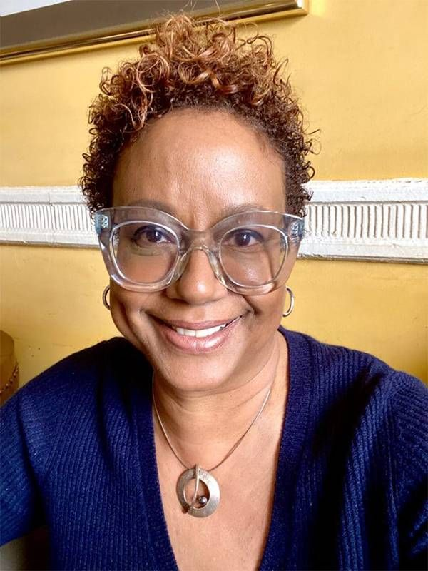 A woman with short curly hair and clear glasses smiling. Nonprofits, Next Avenue