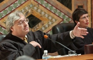 FILE - In this Sept. 22, 2003 file photo, Judge Alex Kozinski, of the 9th U.S. Circuit Court of Appeals, gestures as Chief Judge Mary Schroeder looks on in San Francisco. A decision by a divided three-judge panel of the 9th U.S. Circuit Court of Appeals in San Francisco on Wednesday, Feb. 16, 2014, reinstated a lawsuit filed against YouTube by an actress who appeared in an anti-Muslim film that sparked violence in many parts of the Middle East. The 9th Circuit said the YouTube posting infringed actress Cindy Lee Garcia's copyright to her role, and she, not just the filmmaker, could demand its removal. (AP Photo/Paul Sakuma, Pool, file)