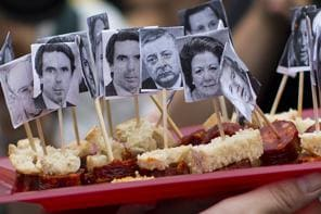 Demonstrators hold trays with bites decorated with small portraits of the government members during a protest in front of the delegation of the Spanish government in Catalonia, in Barcelona, Spain, Thursday July 18, 2013. Spain's prime minister brushed off demands he should resign after text messages emerged showing he had a cozy relationship with a disgraced political party treasurer who amassed 47 million euros ($61 million) in secret Swiss bank accounts. The spectacle of alleged greed and corruption has enraged Spaniards hurting from austerity and sky high unemployment with no end in sight. (AP Photo/Emilio Morenatti)