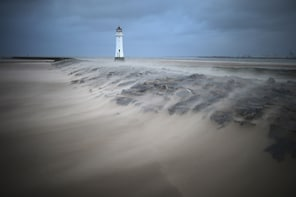 NEW BRIGHTON, UNITED KINGDOM - FEBRUARY 12: A miniature sandstorm whipped up unusually high winds blows across the breakwater next to the Perch Rock lighthouse on February 12, 2014 in New Brighton, United Kingdom. Parts of the UK are experiencing severe storms and rising water levels today, with the Met Office issuing a rare red weather warning - the most severe level of threat - for