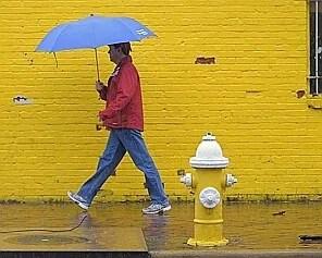 ALEXANDRIA VA APRIL 29: A pedestrian walks in heavy rain on the lower part of Prince Street in Alexandria VA , April 29, 2014. (Photo by John McDonnell/The Washington Post)