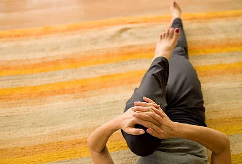 Woman stretching on striped carpet