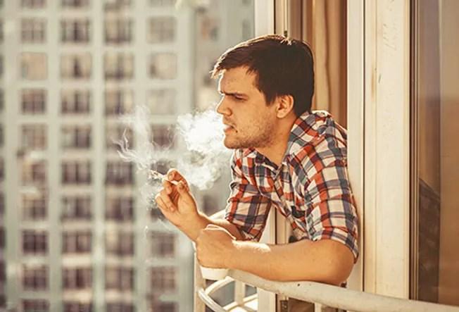 man smoking on balcony