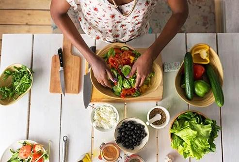 woman preparing salad in kitchen