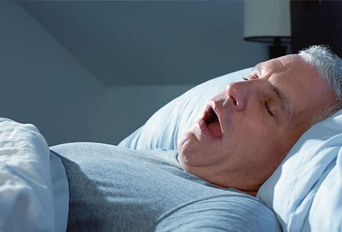 Man snoring in bed at night