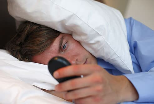 Young business man in bed, looking at mobile phone