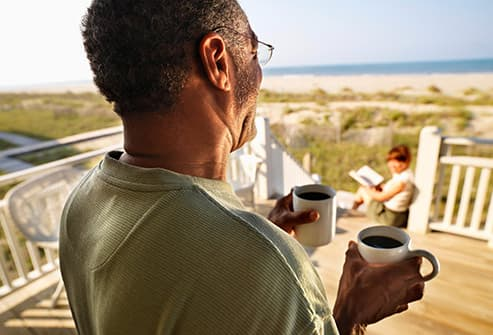 man bringing woman coffee on porch