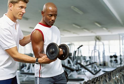trainer helping man with free weights