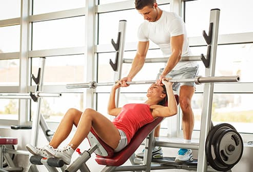 woman lifting empty weight bar
