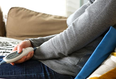woman at home with heating pad