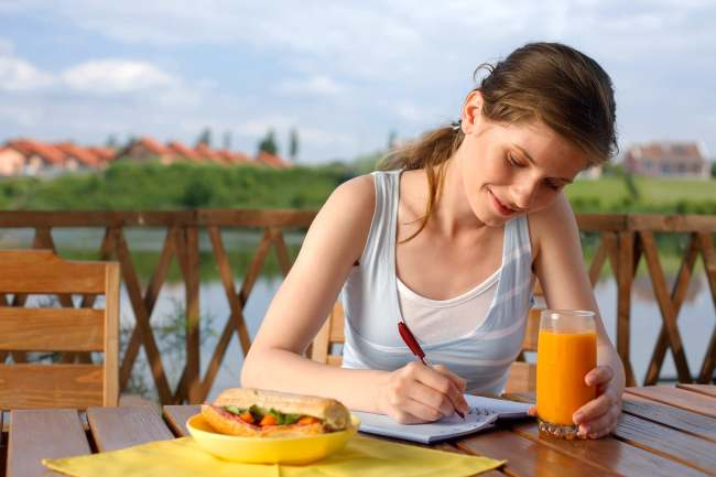 photo of woman writing in food diary
