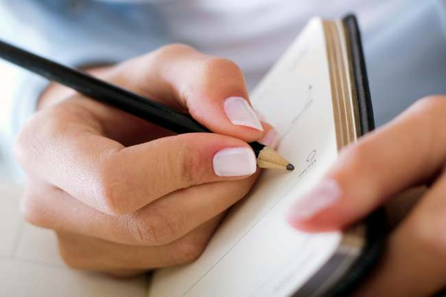 photo of woman writing in notebook