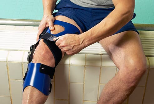 senior man in knee brace by pool
