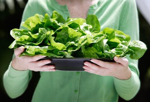 woman holding plate of leafy greens