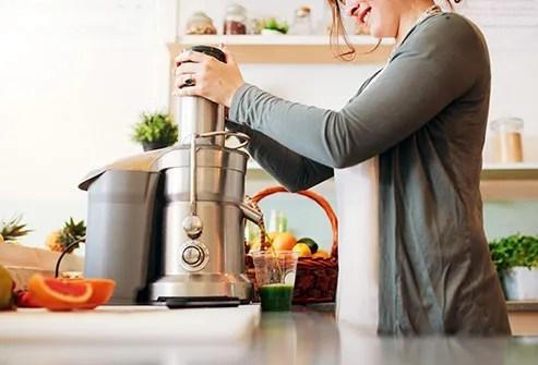 woman using juicer