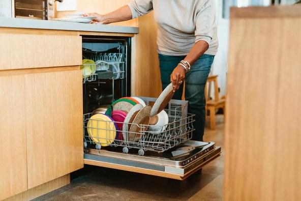 photo of woman loading dishwasher