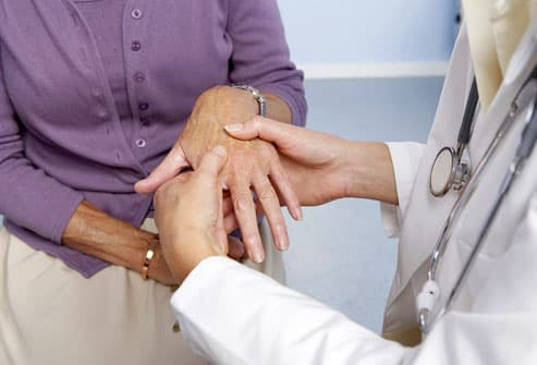 examining hand for signs of rheumatoid arthritis
