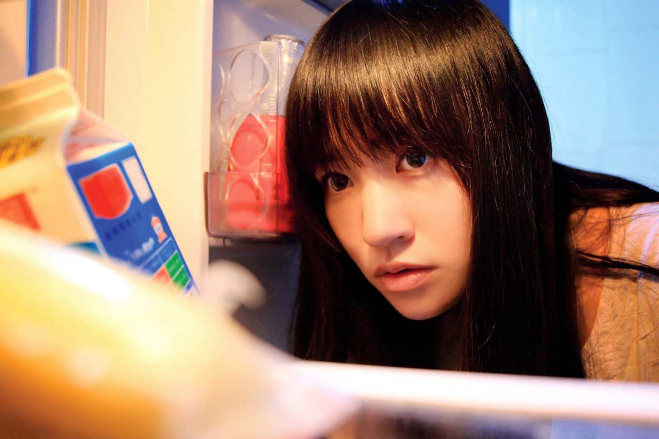 young woman looking in refrigerator