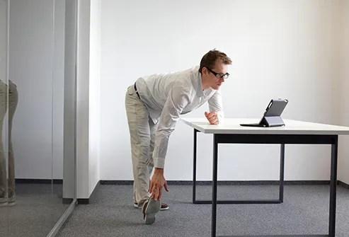 man stretching legs at work
