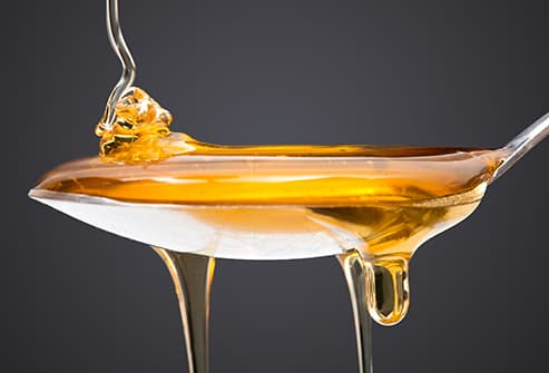 drizzling honey onto spoon
