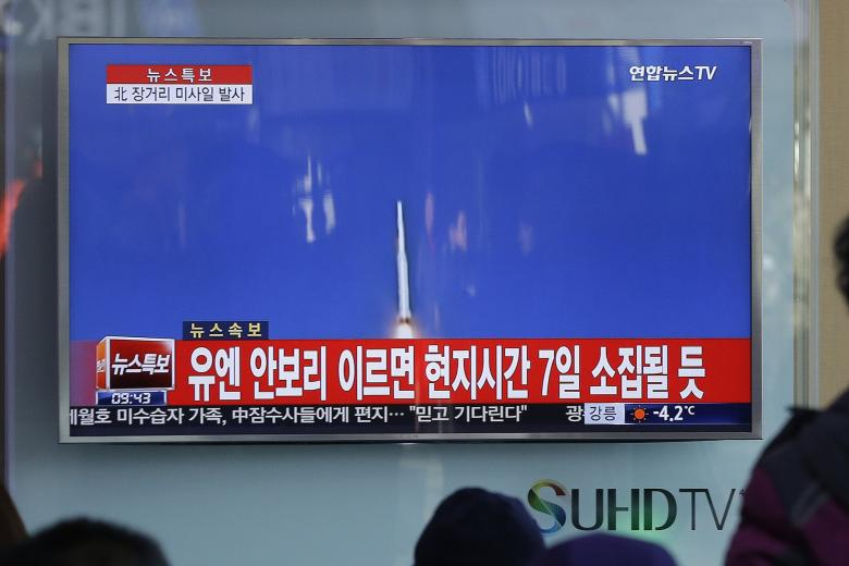 "South Koreans watch a TV news program with a file footage about North Korea's rocket launch at Seoul Railway Station in Seoul, South Korea, Sunday, Feb. 7, 2016. North Korea on Sunday defied international warnings and launched a long-range rocket that the United Nations and others call a cover for a banned test of technology for a missile that could strike the U.S. mainland. The letters on the screen read: ""The U.N. Security Council will hold a meeting on Feb. 7."" (AP Photo/Ahn Young-joon)"