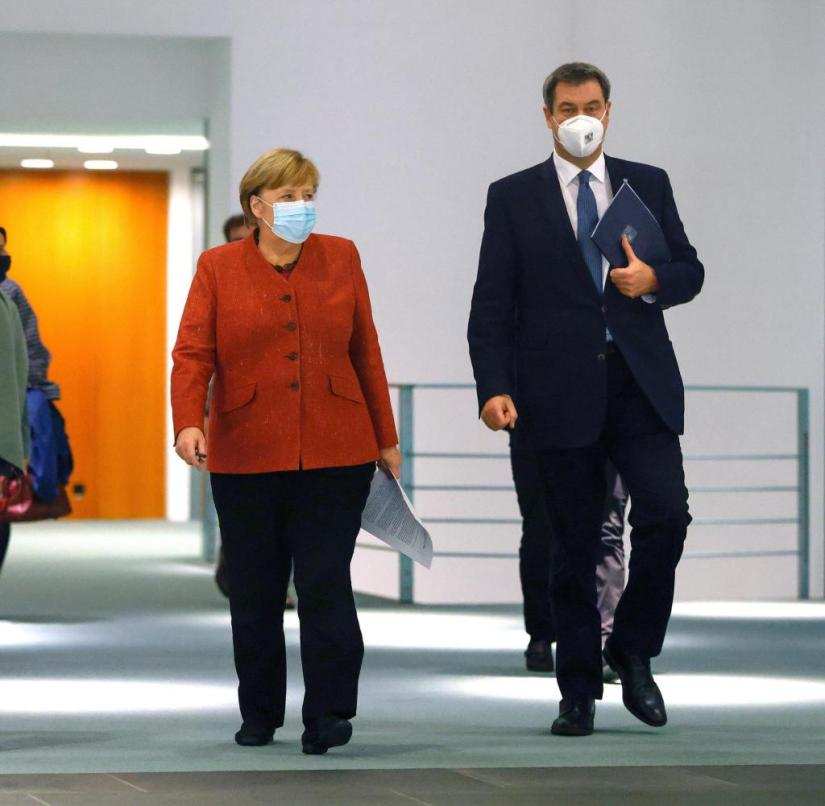 """ARCHIVE - November 16, 2020, Berlin: Federal Chancellor Angela Merkel (CDU, M), Michael Müller (SPD, l), Governing Mayor of Berlin, and Markus Söder (CSU), Prime Minister of Bavaria, leave a room in the Federal Chancellery after a press conference.  Merkel is meeting the prime ministers of the federal states again to discuss further measures to combat the high number of corona infections.  (to dpa """"D for Drosten, Q for lateral thinking: The ABC for the crisis year 2020"""") Photo: Odd Andersen / AFP / POOL / dpa +++ dpa-Bildfunk +++"""