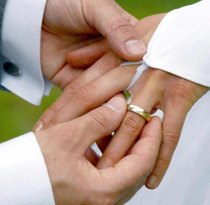 At the wedding ceremony, the groom slips the bride on a wedding ring