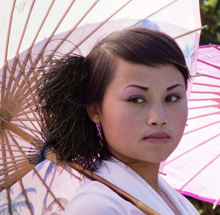 Chinese women use umbrellas to protect their skin from the sun's rays