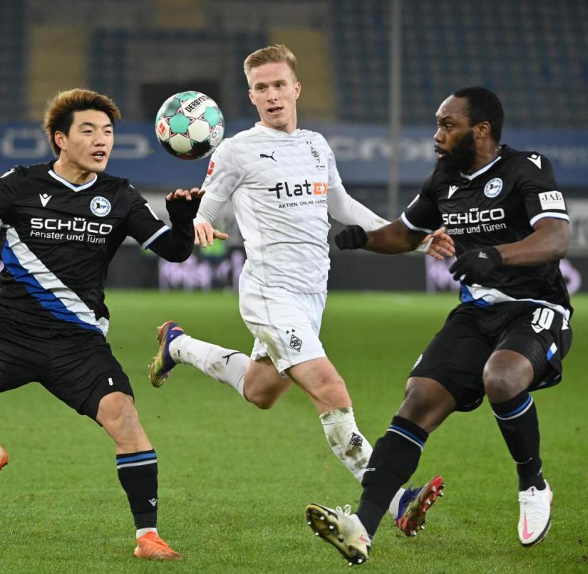 Bielefeld's Ritsu Doan (left) and Reinhold Yabo secure the ball in front of Oscar Wendt