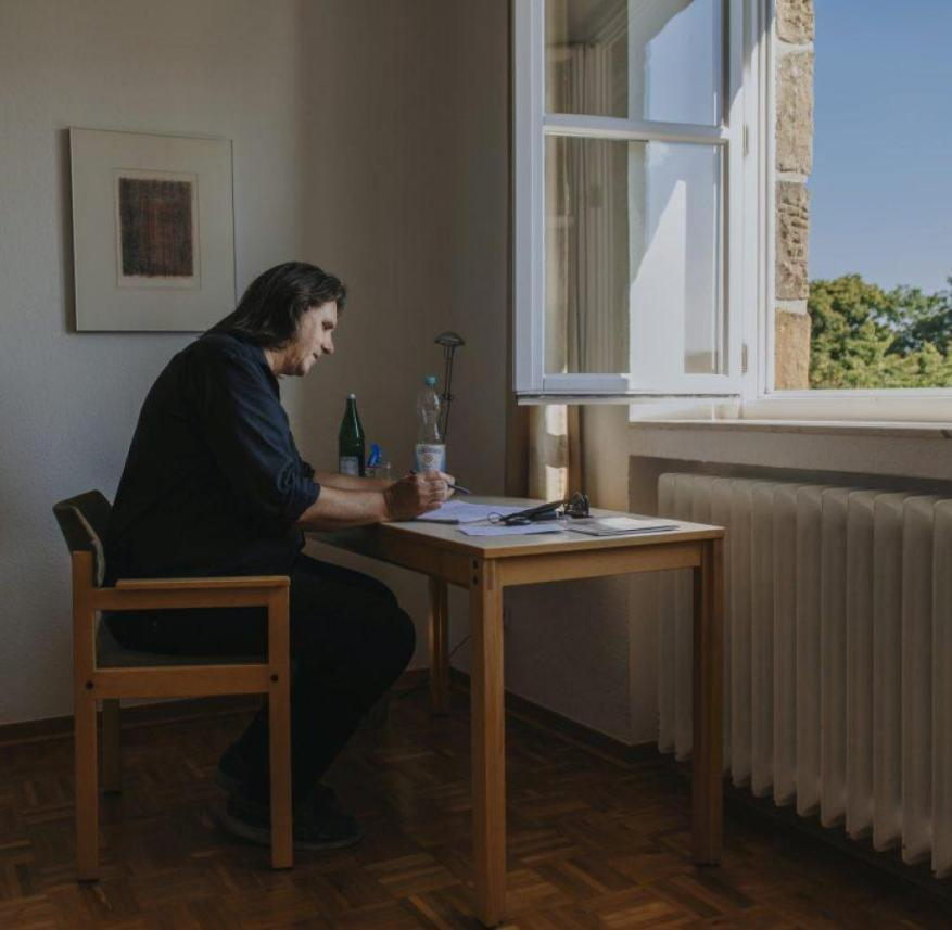Author Stefan Frommann at the desk in his room in Gerleve Monastery.  There is a picture of Jesus on the wall