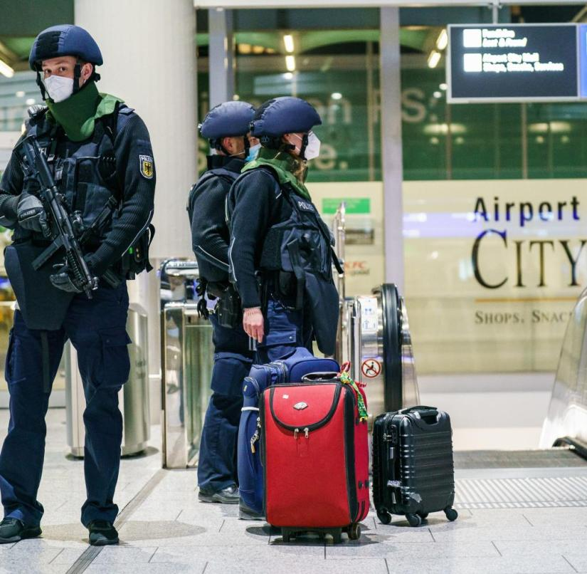 A police officer is standing next to several pieces of luggage in Terminal 1