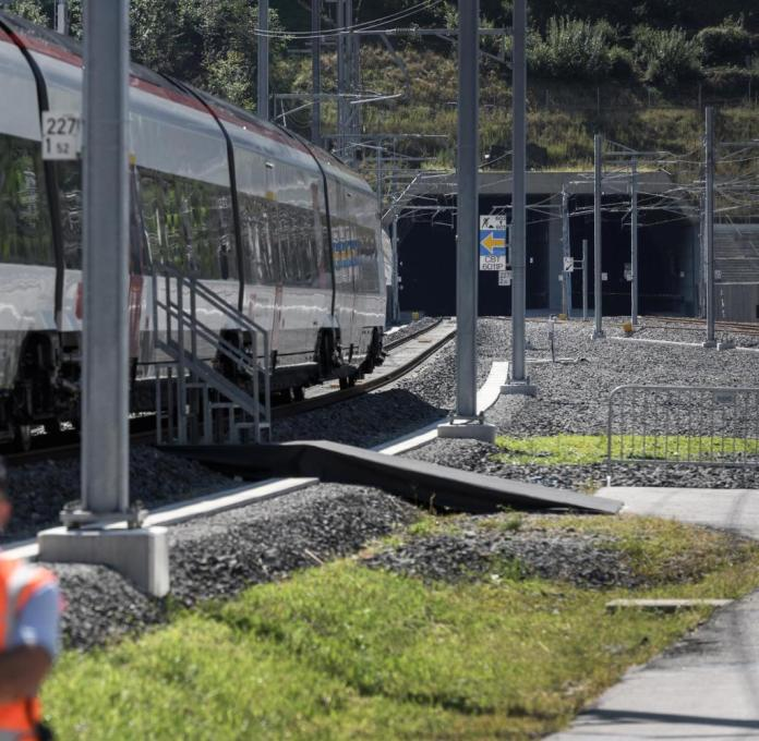 A security stands next to a train on September 4, 2020, in Camorino, southern Switzerland, during the inauguration of the Ceneri Base railway tunnel. - The two single-track 15,4 km long tunnel through the Alps (NRLA) aims to mainly reduce transalpine truck traffic. The rail service is expected to start in December 2020. (Photo by Fabrice COFFRINI / AFP) (Photo by FABRICE COFFRINI/AFP via Getty Images)