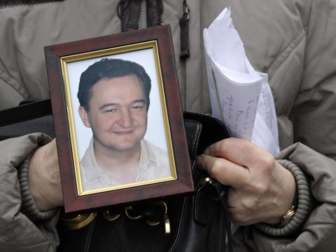 This is a Monday, Nov. 30, 2009 file photo showing a portrait of lawyer Sergei Magnitsky who died in jail, as it is held by his mother Nataliya Magnitskaya, as she speaks during an exclusive interview with the AP in Moscow. Russian investigators said Tuesday, Aug. 2, 2011, they reopened a criminal probe against the dead lawyer who claimed to have uncovered a massive tax fraud by corrupt police officers.