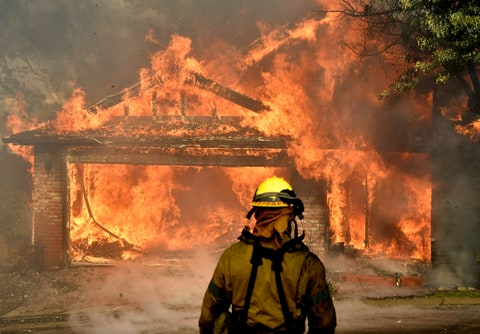 Firefighters battle to save one of many homes burning in an early-morning Creek Fire that broke out in the Kagel Canyon area in the San Fernando Valley north of Los Angeles