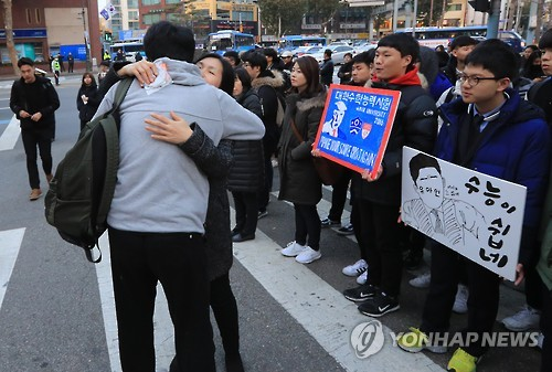 A test-taker gets encouragement from his mother in front of a high school in central Seoul on Nov. 17, 2016, before entering the school to sit for the state-administrated college entrance exam that takes place nationwide the same day. Some 605,000 students nationwide are taking the test to enter college in the spring semester that begins in March. (Yonhap)