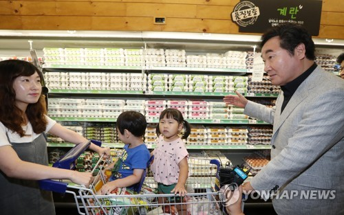 Prime Minister Lee Nak-yon (R) speaks with a South Korean citizen about egg products at a discount store in Sejong on Aug. 19, 2017. (Yonhap)