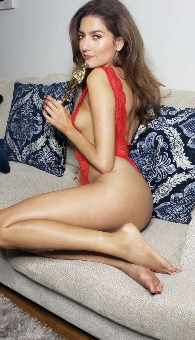 Blanca Blanco holds a golden statue while posing for photos in a Hot red lace bodysuit hd Photos