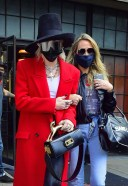 Miley Cyrus Hot Photos in a red trench coat paired with black leather pants and a black hat in New York