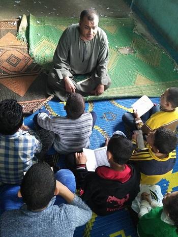 الشيخ محمد أثناء تعليم الأطفال التجويد