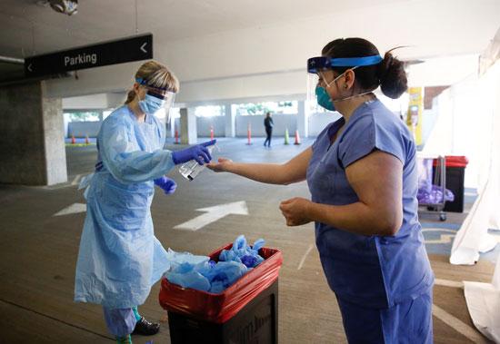 ممرضة-تمنح-زميلتها-المطهرات-اليدوية-لتغير-معداتها-الوقائية-بعد-اختبار-مريض-في-عيادة-متنقلة