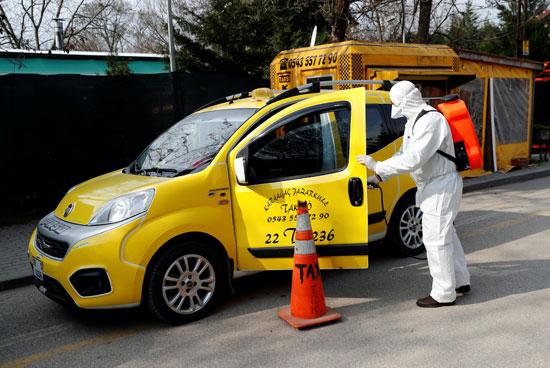 عاملة-بلدية-ترتدي-بدلة-واقية-تعقم-سيارة-أجرة-في-منطقة-كاراجاك-في-أدرنة